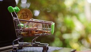 close up toy shopping cart with bitcoin on notebook,