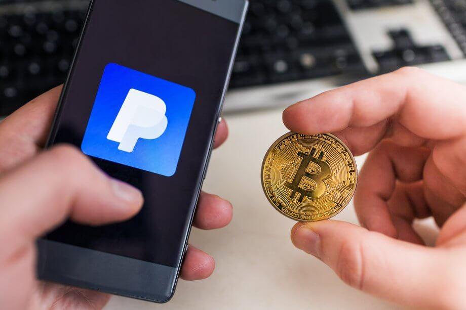 Smartphone mit PayPal-Logo, daneben eine Bitcoin-Münze
