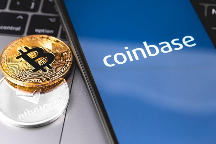 Bitcoin- und Ethereum-Münzen neben Smartphone mit Coinbase-Logo auf dem Bildschirm
