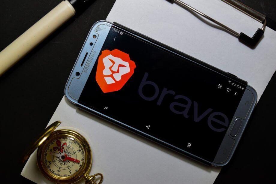 Smartphone auf Klemmbrett mit Kompass, das Display ziert das Logo des Brave Browser