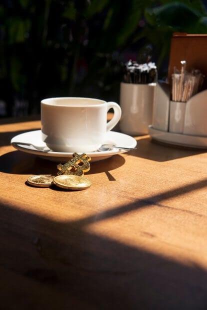 Kaffeetasse und Bitcoin-Münze