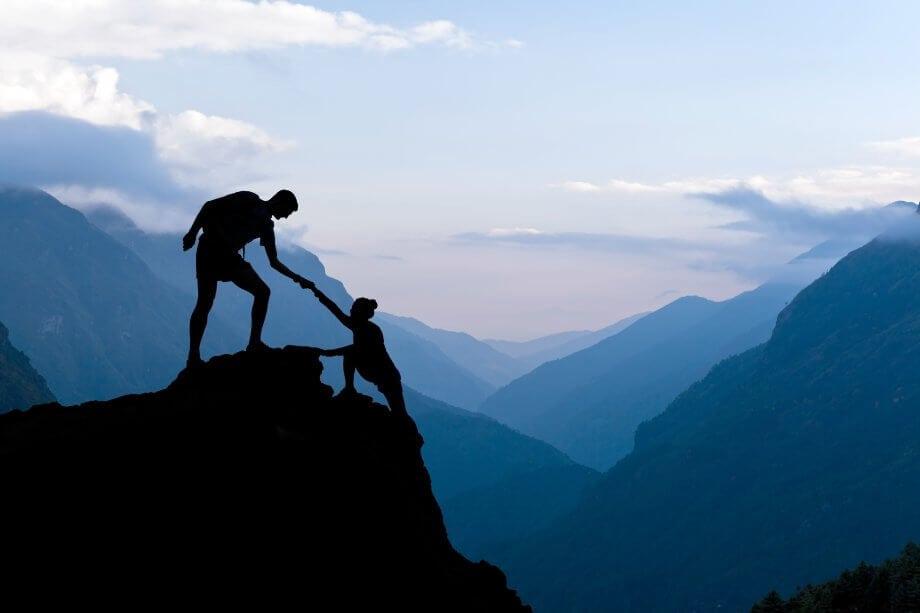Teamwork Ehepaar helft Hand Vertrauen Hilfe Silhouette in den Bergen, Sonnenuntergang. Team von Bergsteigern Mann und Frau Wandern, helfen einander auf der Bergspitze, schöne Landschaft im Himalaya Nepal