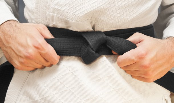 mensch-zieht-schwarzen-gürtel-zu