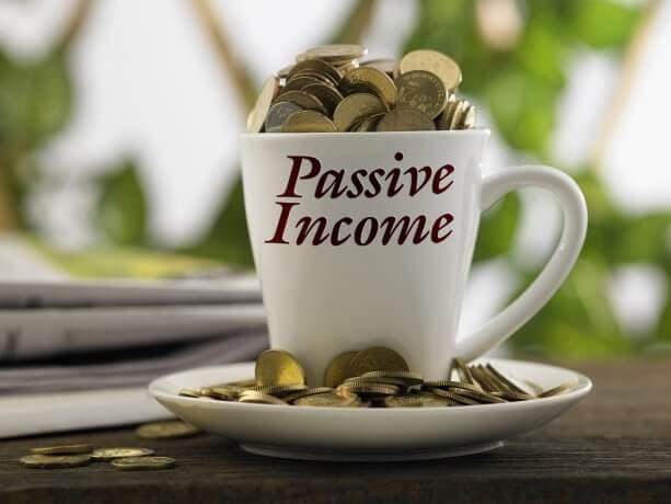 """Zum Überquellen mit Münzen befüllte Kaffeetasse mit dem Aufdruck """"Passive Income"""" (Passives Einkommen)"""