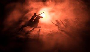 Weltkriegsoffizier (oder Krieger) reiten auf dem Pferd mit einem Schwert, das bereit ist zu kämpfen, und Soldaten auf dunkelnebelfarbenem Hintergrund. Schlachtfeld von Kampfsoldaten. Selektiver Fokus