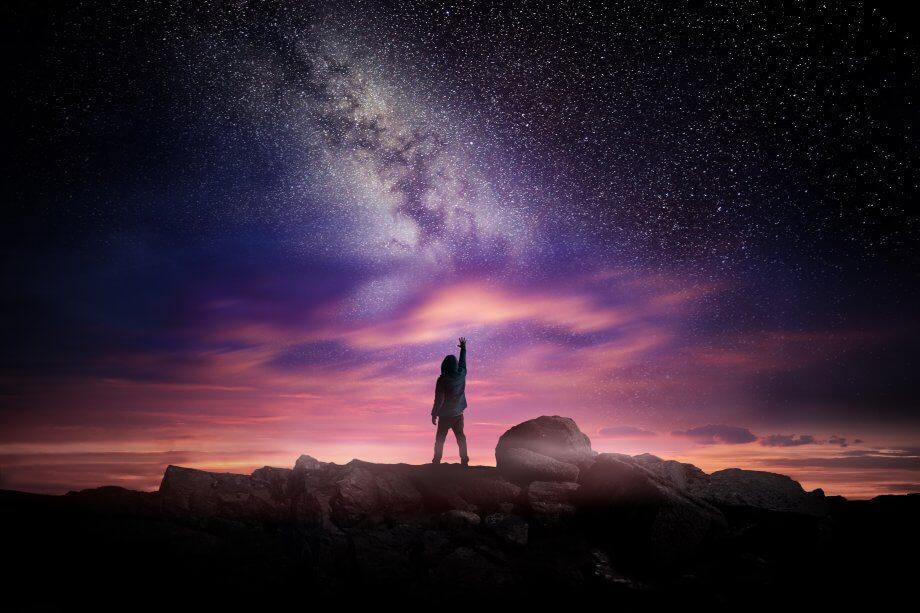 Ein Mensch der nach den Sternen greift vor einem rosanen Hintergrund. Frei nach dem Motto: Ein Idiot, der nach den Sternen greift, ist immer noch ein Idiot