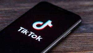 das symbol der tiktok app auf einem schwarzen smartphone, das auf einem braunen holztisch liegt