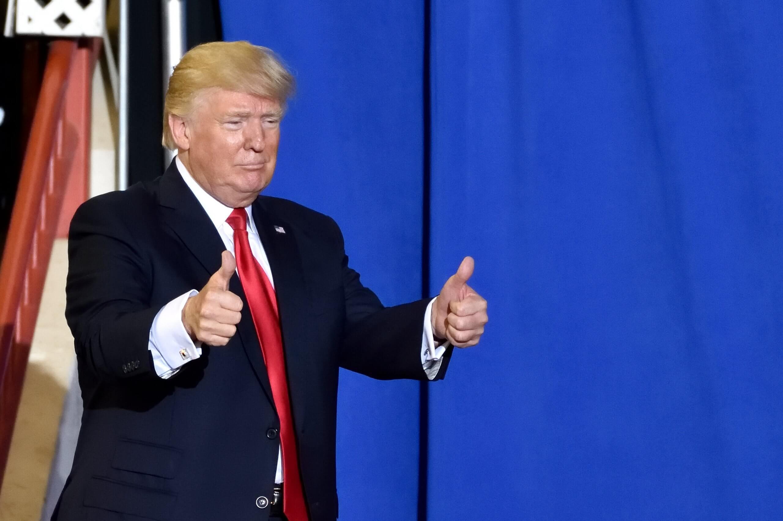 Donald Trump, bekannt als US-Präsident, zeigt beide Daumen nach oben und schaut etwas dümmlich aus der wäsche