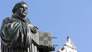 Das Bild zeigt eine Statue Martin Luthers, der seine Thesen präsentiert.