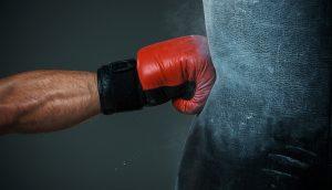 Mensch schlägt auf Boxsack ein