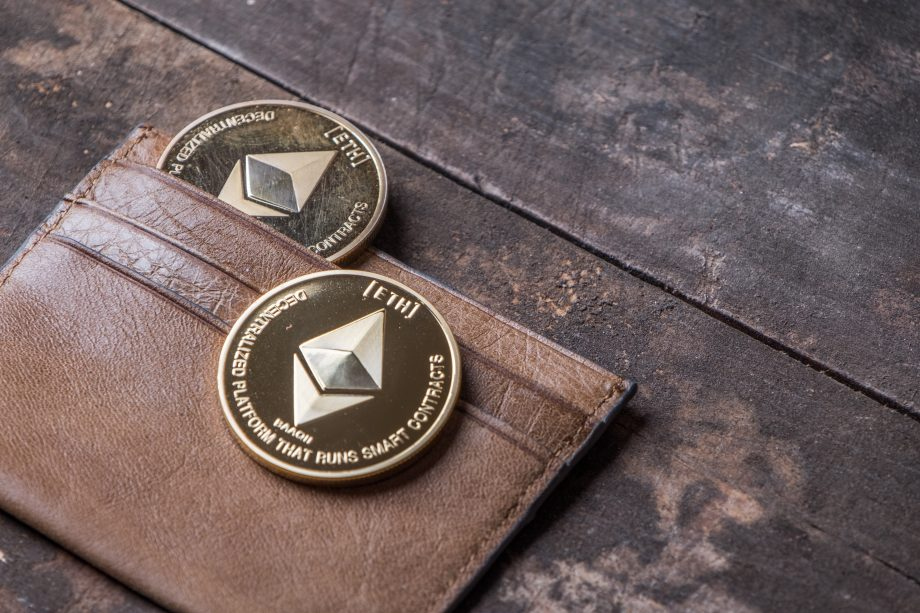 Ethereum Münzen liegen in einer Briefbörse auf einem Holztisch