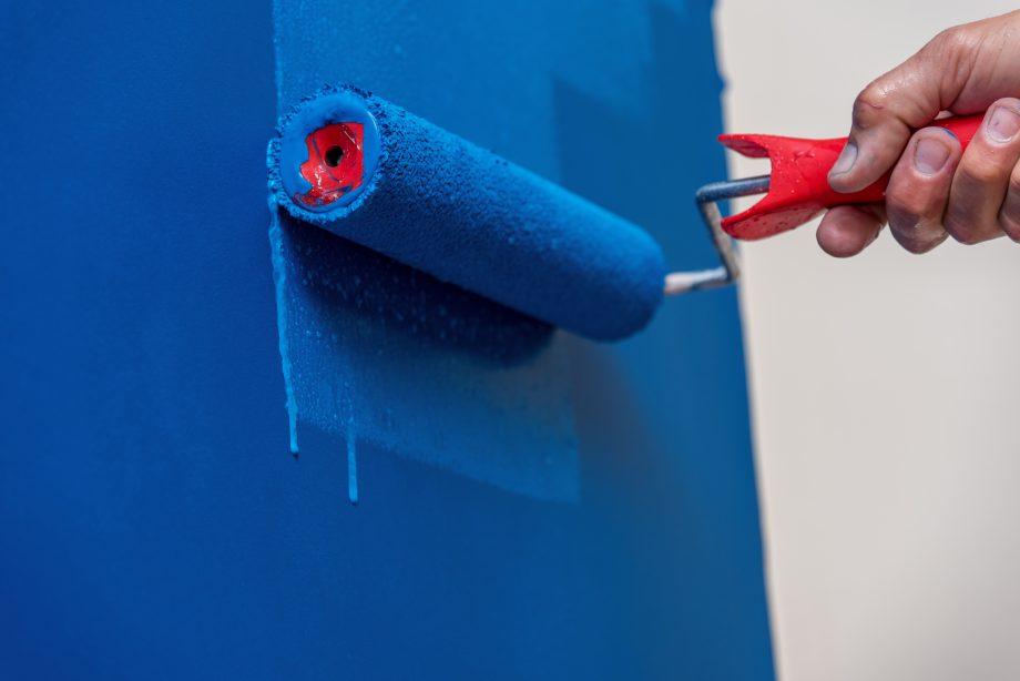 Mensch streicht Wand mit blauer Farbe