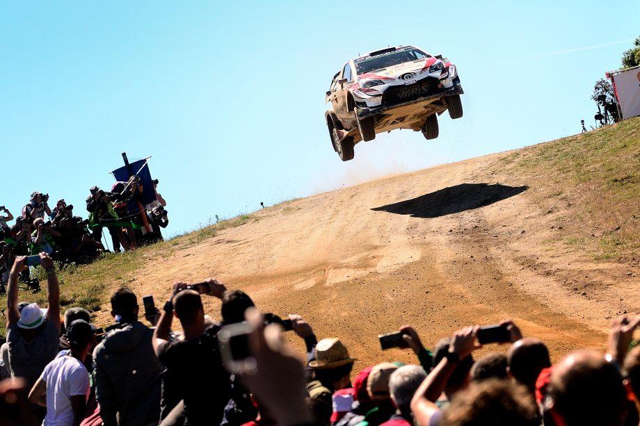 Rennauto springt bei einer Rallye über einen Hügel