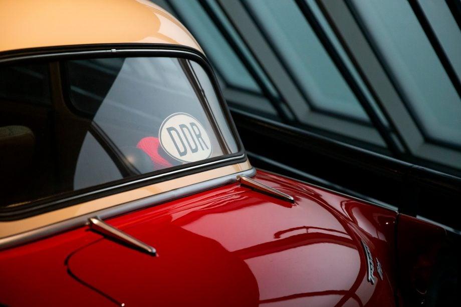 Auf dem Bild ist ein rot-gelber Trabant, kurz Trabbi zu erkennen, ein Symbol der DDR und damit der dortigen Planwirtschaft.