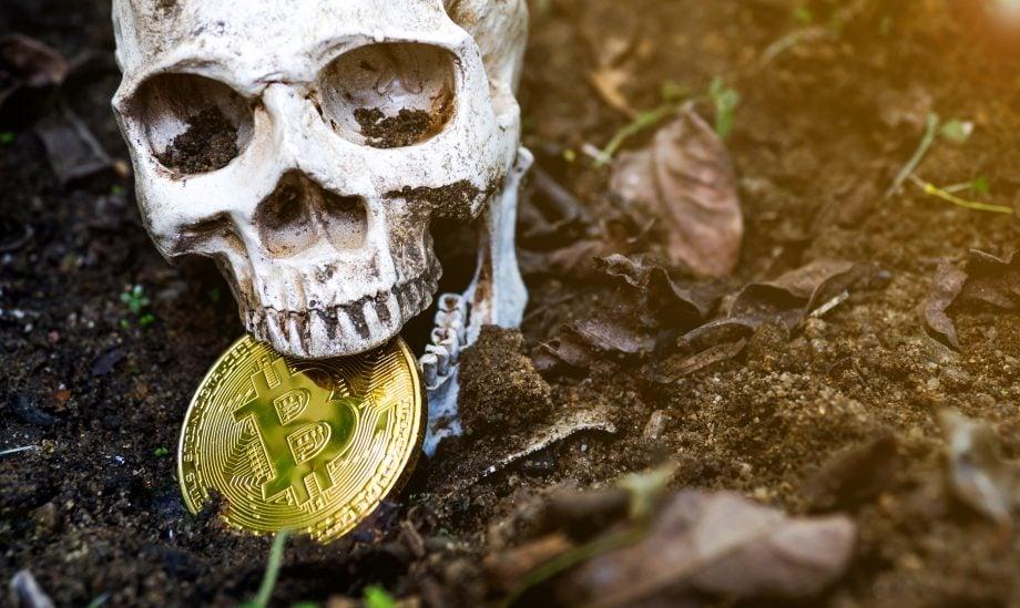 Künstlicher Totenkopf mit Bitcoin-Münze zwischen den Kiefern