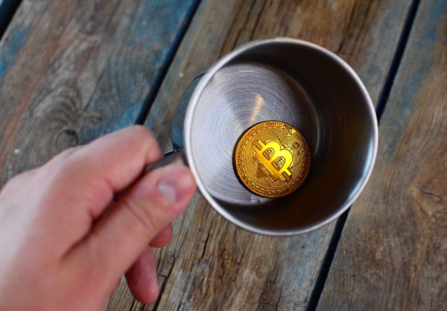 Bitcoin-Münze in einem leeren Metallbecher