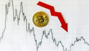 Bitcoin-Münze auf Chart mit rotem Pfeil der abwärts zeigt