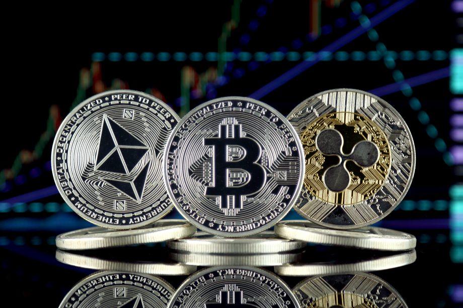 Bitcoin-, Ripple- und Ethereum-Münze vor Chart