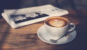 Dekorativer Kaffee mit Latte-Art vor zusammengefalteter Zeitung auf Holztisch.