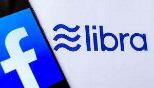Facebook-Logo auf Smartphone vor Libra-Hintergrund