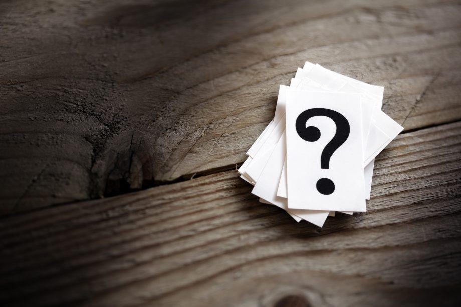 Zettel mit Fragezeichen liegen auf einem Holztisch