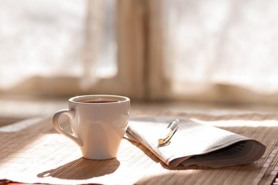 kaffeetasse-neben-einer-zeitung-auf-einem-holztisch