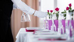 Kellner richtet Geschirr auf einem Tisch