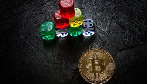 Spielwürfel neben Bitcoin-Münze