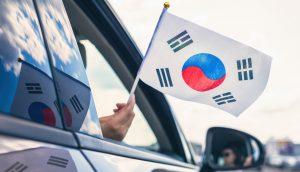 Südkorea-Flagge, die aus einem offenen Autofenster gehalten wird