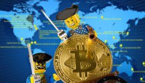 Lego-Piraten mit Bitcoin-Münze vor Weltkarte