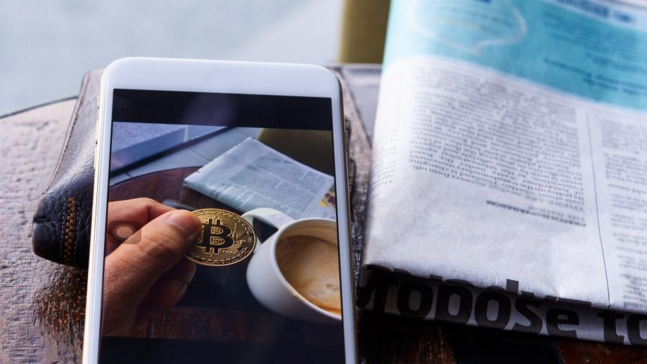 Morning news cryptocurrency with newspaper and bitcoin on mobile screen.