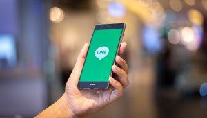 Eine Hand hält ein Smartphone, auf der die LINE App geöffnet ist.
