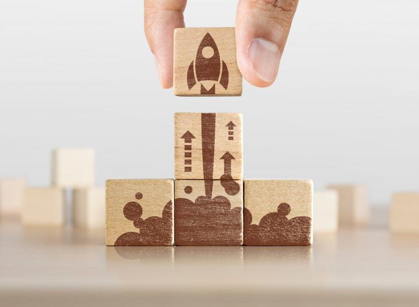 Unternehmensgründung, Start, neues Projekt oder neues Ideenkonzept. Hölzerne Blöcke mit Raketengrafik in Pyramidenform angeordnet und ein Mann hält den oberen.