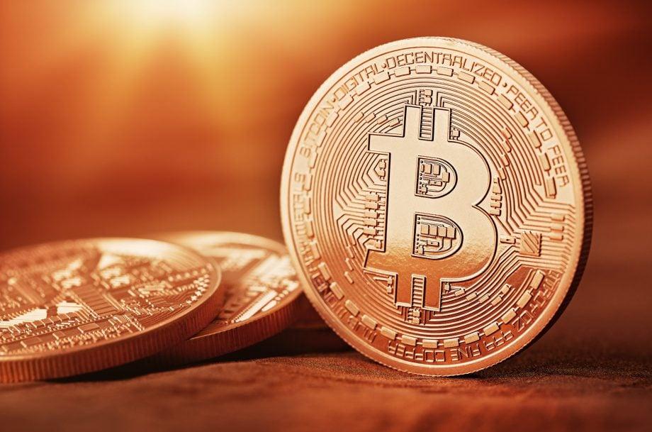 Physische Repräsentanz einer Bitcoin-Münze auf güldenem Hintergrund.