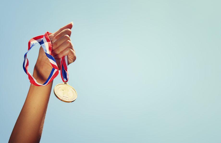 Frau, die Hand hob, hielt Goldmedaille gegen den Himmel. Preis- und Siegeskonzept