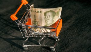 hopping cart with a paper banknote of One Chinese Yuan and face of leader Mao, as a symbol of the modern international economy