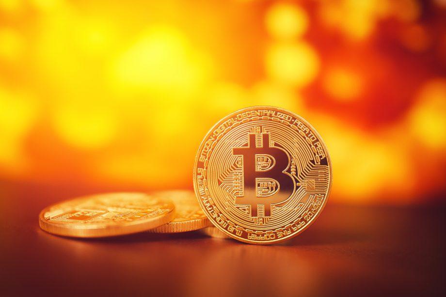Bitcoin-Münze vor gelben Hintergrund.