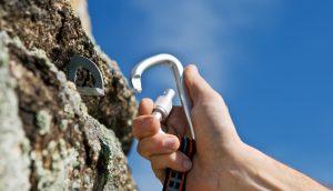 Hand befestigt Seil beim Bergsteigen