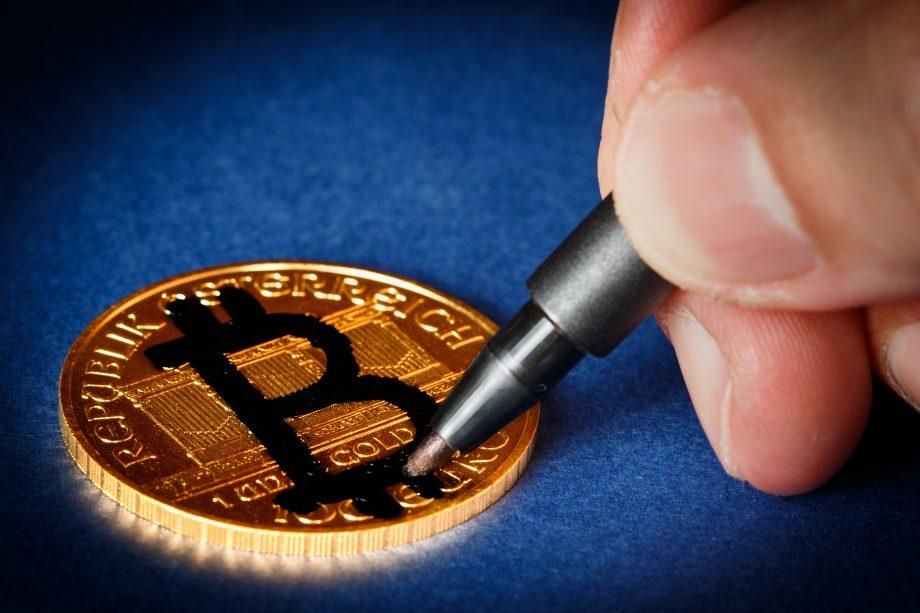 Goldunze wird mit Bitcoin-Zeichen übermalt