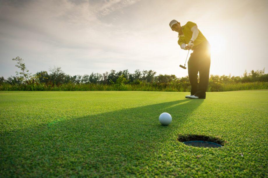 Golfer locht einen Ball ein.
