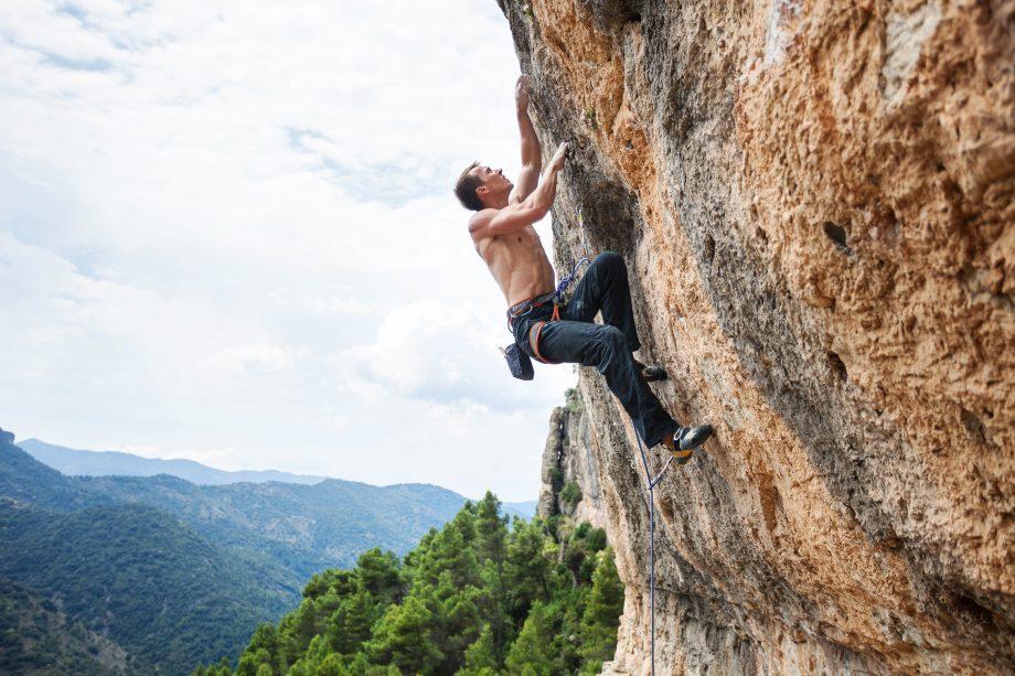 Mann klettert an Felswand hoch