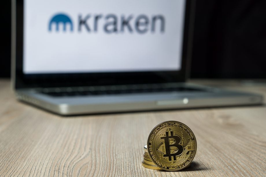 Bitcoin vor Laptop mit Kraken-Logo
