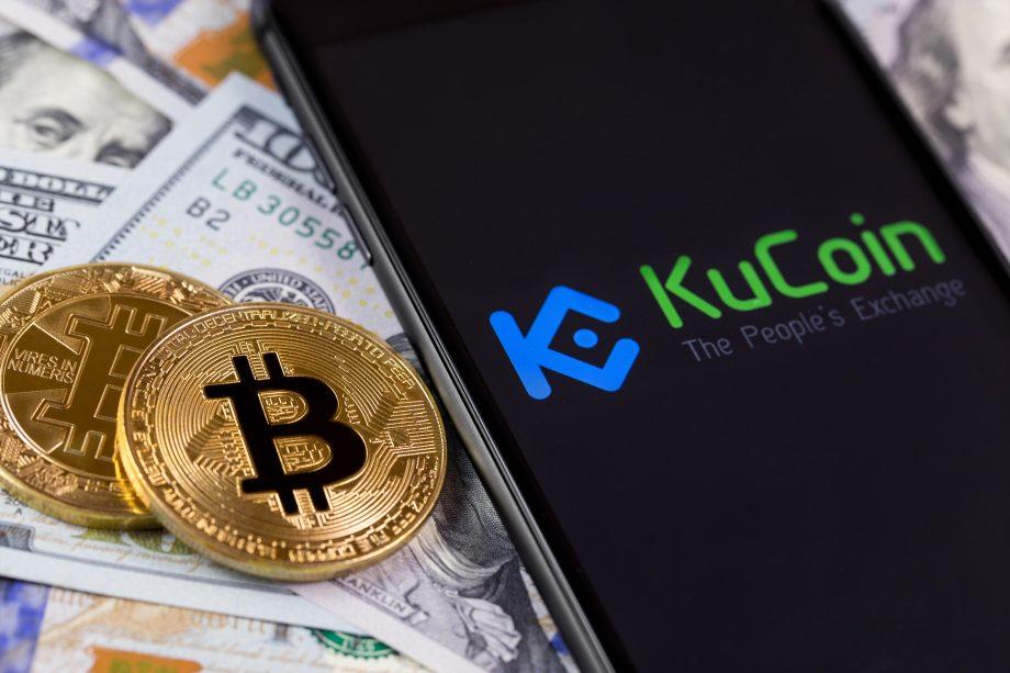 Bitcoin liegen neben Geld und KuCoin-Smartphone