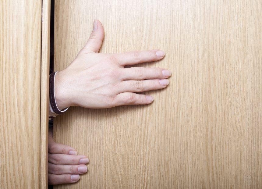 Hände stecken im Türrahmen