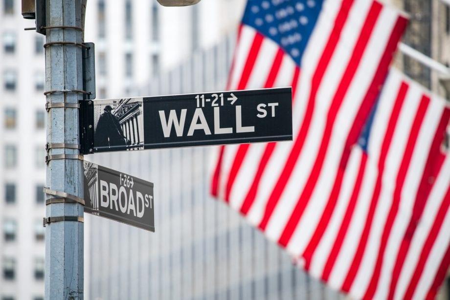 Wall-Street-Schild mit US-amerikanischer Flagge im Hintergrund