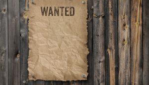 Wanted Schild an Holzzaun genagelt