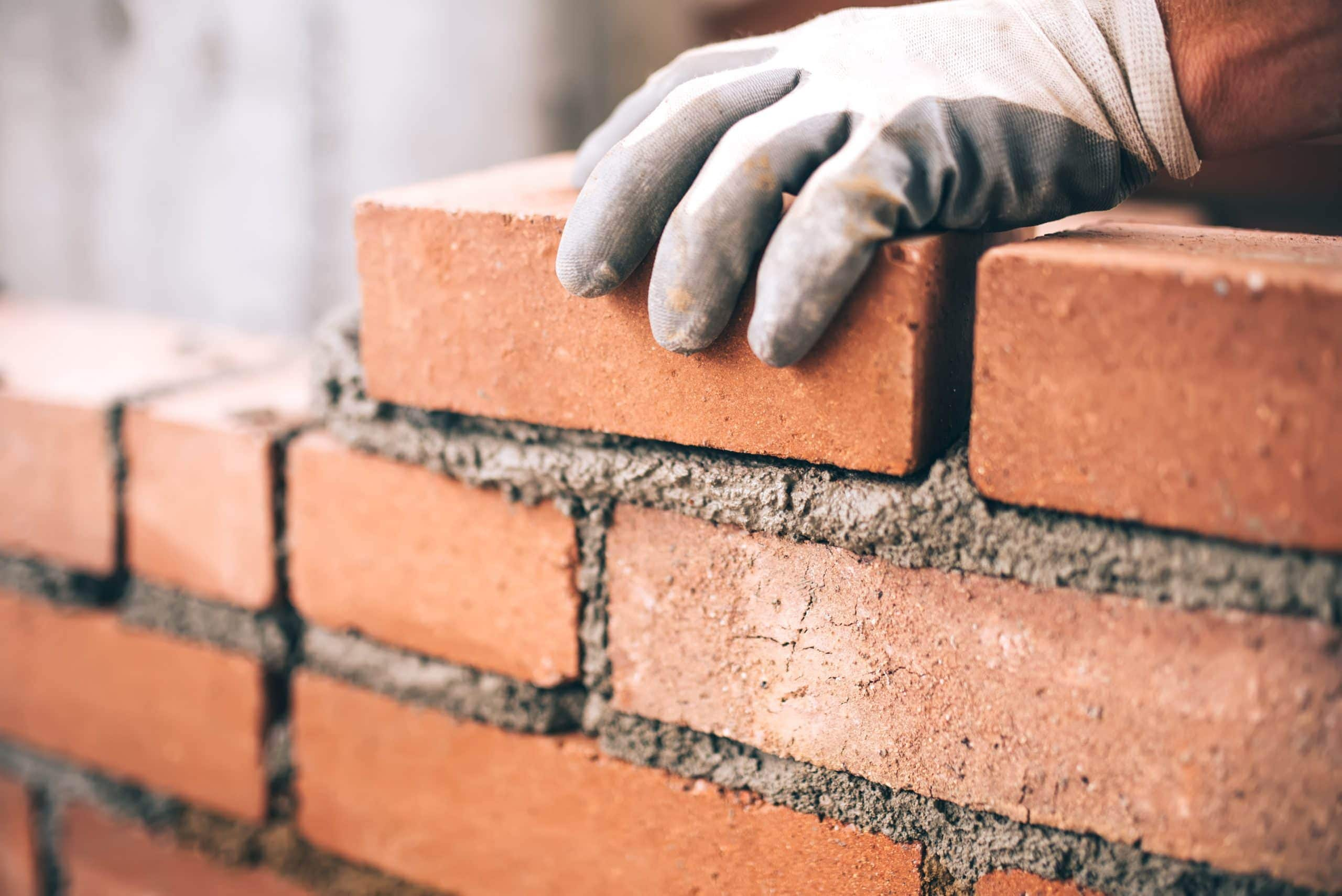 Mensch baut Mauer aus Ziegelsteinen