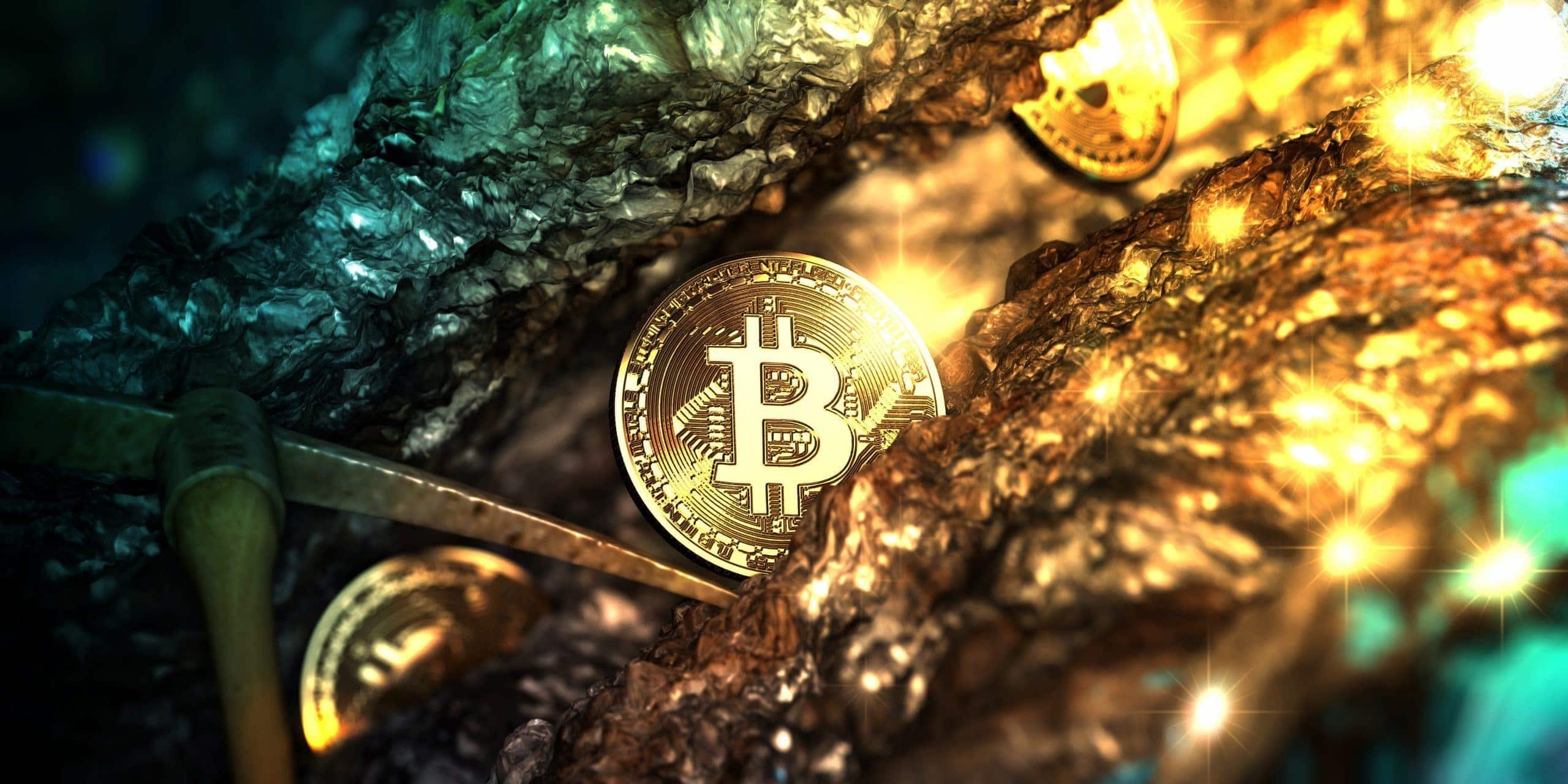 Eine Bitcoin Münze liegt in einer Goldmine neben einer Hacke.