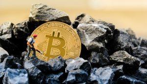 Bitcoin-Münuze auf einem Kohlehaufen, daneben die Modellfigur eines Minenarbeiters (Symbolbild Bitcoin Mining / Proof of Work)