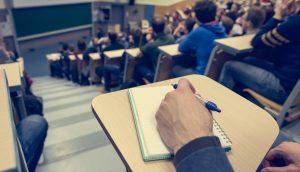 Hörsaalgebäude in dem Studenten sitzen und mitschreiben.